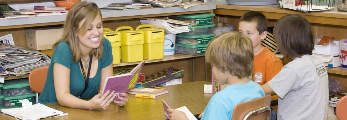 Student teacher reading to group of children